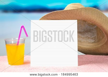 Summer offer background template for promotion and sales. Yellow cocktail and brimmed hat on towel with beautiful paradise view on beach. Empty white paper card with free blank copy space for content.