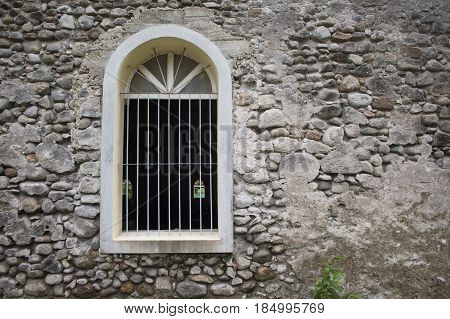 White window in old grey stone wall. Old medieval architecture. ANcient fortification photo. Rustic stone wall with cement plaster. Durable paving of old building. Grey stone wallpaper or background