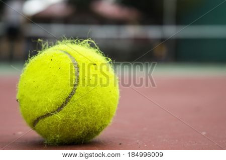 Yellow tennis ball on red court. Fluffy felt tennis ball closeup photo. Summer outdoor sport concept. Tennis game playing. Tennis net and player on background. Sport match or competition. Active life