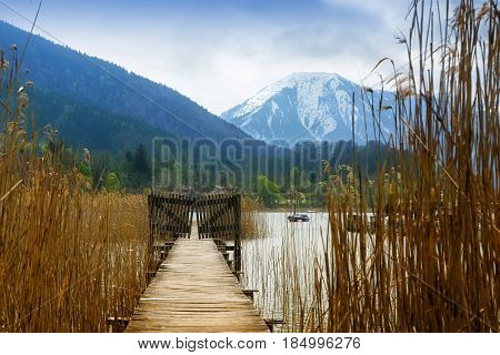 Wooden jetty with gate in the tegernsee lake snow-covered mountains in the background landscape in the famous tourist resort in the bavarian alps bavaria germany europe