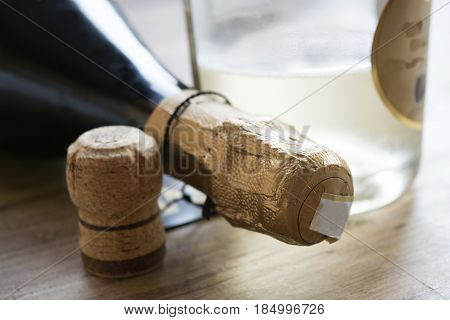 detail of a bottle of bubbly white wine next to a cork