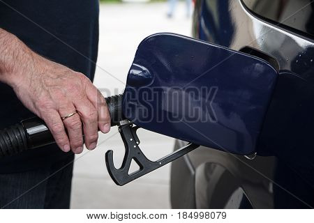 Man's hand holds a fuel pistol and refuel his car with gasoline or diesel at the petrol station concept for environmental protection or rising oil price