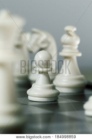 Chess figure pawn on board. Chess game play closeup. Chess figures with focus on pawn. Bishop Knight and Queen on background. Vertical image of checkmate. Intellectual board game. Strategic advantage