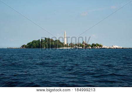 White Lighthouse Standing On An Island With Natural Rock Formation And Green Vegetation In Belitung