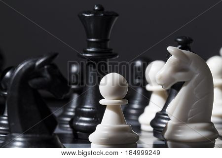 Black and white chess figures on chessboard. Checkmate game process. Black queen and Knight over white pawn. Business strategy advantage concept. Tactic threat in team attack. Smart table game photo