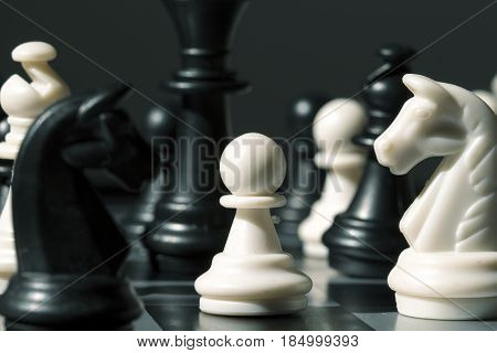 Chess figure pawn on the board. White pawn in black figures on chessboard. Antagonist concept. Black queen over white pawn. Competitive business strategy. Tactic table game checkmate process photo