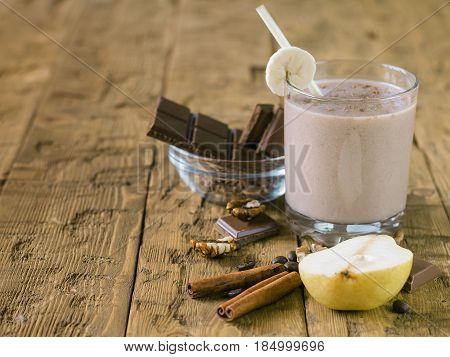 Cinnamon, Pear And Chocolate Smoothie On A Wooden Table.