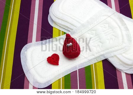 Funny blood crochet drop and heart with menstruation sanitary soft pads napkins. Woman hygiene protection. Woman critical days gynecological menstruation cycle. Medical conception photo