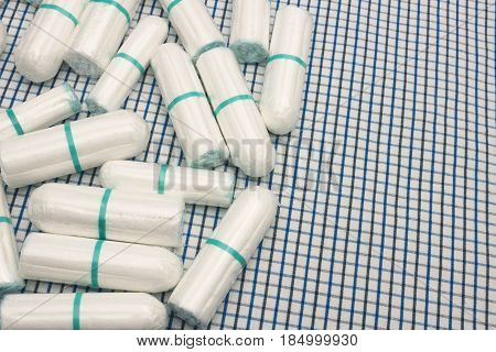Menstruation sanitary clean cotton tampons on the plaid coverlet. Woman hygiene protection. Soft tender protection for woman critical days gynecological menstruation cycle. Place for text copyspace