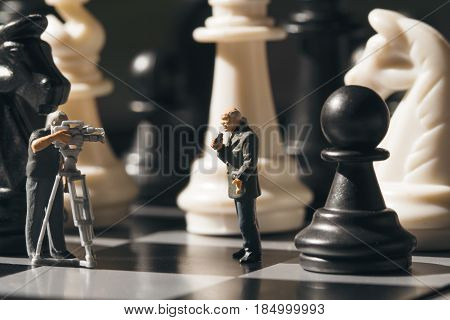 Chess game online broadcast. Filming chess game process. Miniature journalists on chessboard. Chess game process. Chess playing story. Chessmate reporters scene. Black and white figures on game board