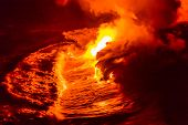Lava flow pouring into Hawaii ocean at night. Lava falling in ocean waves in Hawaii from Hawaiian Kilauea volcano at night. Molten lava washed by the pacific ocean water crashing in, Big Island, USA. poster