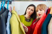 girl with stylist choosing her fashion outfit. Women looking at clothes hanging deciding what to wear. Analysis of wardrobe. Fashion stylist consultation. Master class how to stylishly clothing poster