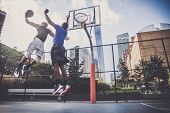 Two afroamerican athlethes playing basketball outdoors - Basketball athlete training on court in New York poster