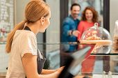 Polite confectionery worker is greeting new customers coming in door. Girl is standing at counter and smiling poster