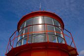 Red lighthouse`s lamp on the blue sky background poster