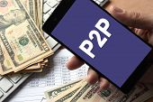Smartphone in hand with message P2P. Peer to peer lending concept. poster