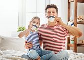 Happy father's day! Dad and his child daughter are playing and having fun together. Beautiful funny girl and daddy have mustaches on cups. Family holidays and togetherness. poster