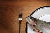 A trout on a plate with a fork. poster