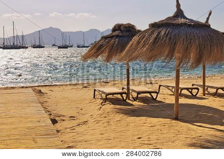 Empty deck chairs and umbrellas on the beach in Port de Pollenca, Mallorca, Balearic islands, Spain