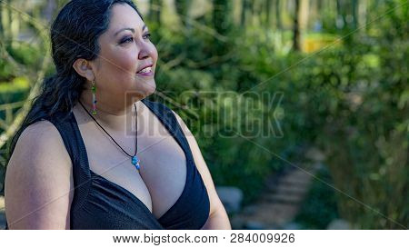 Sexy mature latin Mexican woman with long black hair wearing a deep neckline sexy black dress looking to the right with blurred green vegetation in the background poster