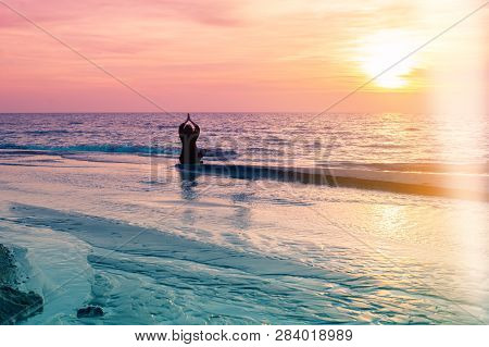 Yoga Silhouette. Meditation Fitness Woman Sitting On Beach During Amazing Sunset. Healthy Lifestyle.
