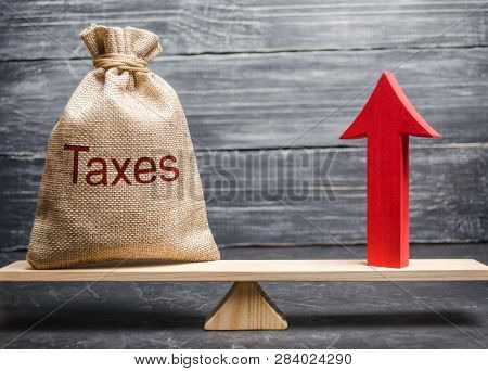 A Bag With The Inscription Taxes And A Red Arrow Up On The Scales. The Concept Of Profit Growth And