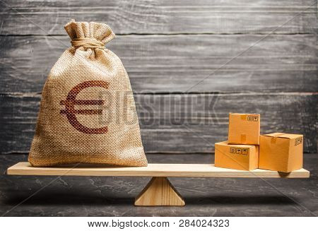 A Bag Of Euro Money And A Bunch Of Boxes On The Scales. Economic Relations Between Subjects, The Glo