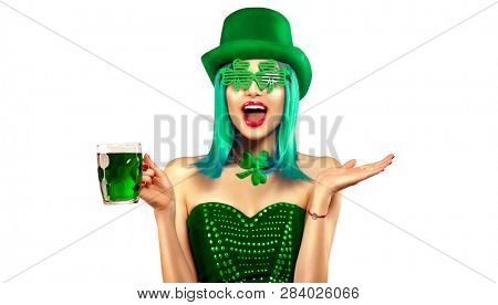 St. Patrick's Day leprechaun model girl in green hat holding mug of Green Beer pint over white background and pointing hand, Smiling. Patrick Day pub party, celebrating. Glass of Green beer. Ads