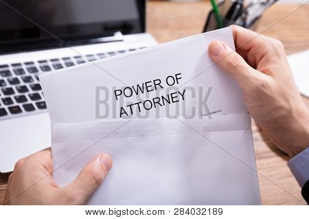 Person Removing Power Of Attorney Document From Envelope
