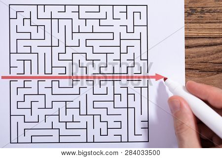 Person Solving Maze Puzzle With Red Marker