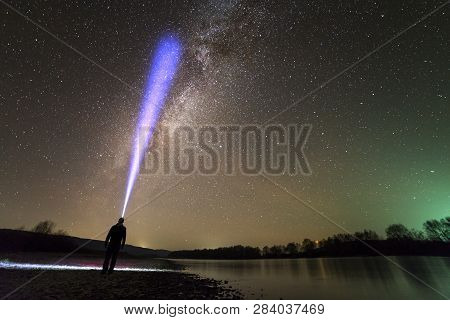 Back View Of Man With Head Flashlight Standing On River Bank, Long Blue Beam Across Beautiful Dark S