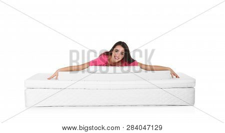 Young Woman Lying On Mattress Pile Against White Background