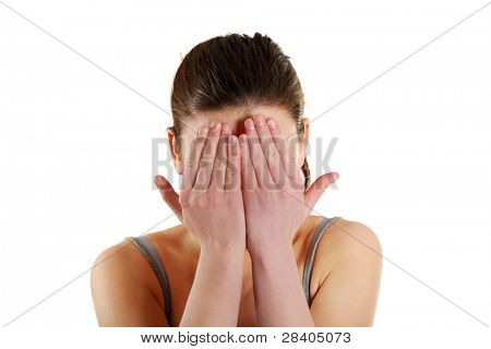 Frighten girl hides her face in hands, isolated on a white background