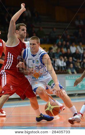 KAPOSVAR, HUNGARY - NOVEMBER 19: Nik Raivio (in white) in action at a Hugarian National Championship  basketball game Kaposvar (white) vs. Paks (red) November 19, 2011 in Kaposvar, Hungary.