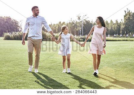 Family Walk. Family Of Three Walking On Grassy Field Looking At