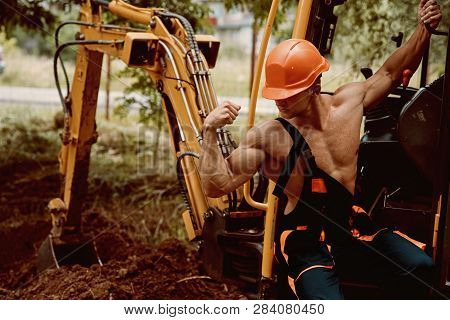 Employee Concept. Employee Flex Biceps And Triceps Muscle. Strong Employee At Excavator Cabin. Emplo