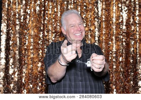 Man in a Photo Booth. A Caucasian man smiles and has fun posing in a Photo Booth with a Gold Sequin curtain. White male wearing handcuffs points to the camera and smiles.