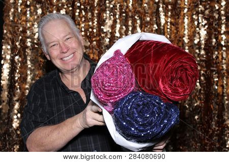 Man in a Photo Booth. A Caucasian man smiles and has fun posing in a Photo Booth with a Gold Sequin curtain. White male holds diffrent background options and points to the camera and smiles.