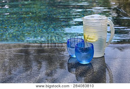 Glasses Of Water With Lemon And Jar On The Edge Of Infinity Swimming Pool