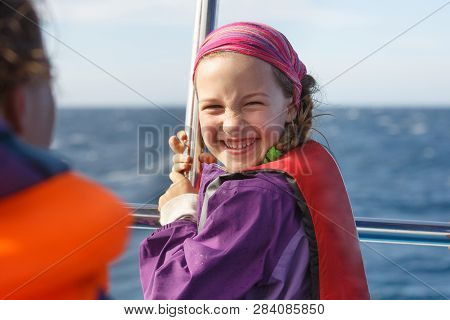 Smiling Girl In Safety Jacket On A Boat Trip. Family On A Blue Whale Watching Trip.