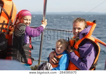 Family On A Blue Whale Watching Trip. Smiling Girl In Safety Jacket On A Boat Trip. Mother Holding B