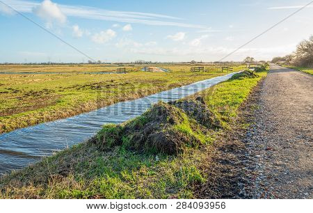 Long Ditch In A Dutch Polder Landscape. The Ditch Has Been Cleaned Recently And The Waste Has Been P