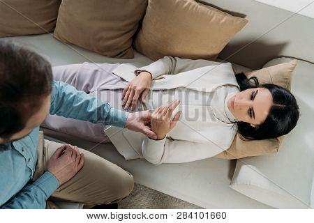 Overhead View Of Hypnotist Holding Wrist Of Young Woman Lying In Couch