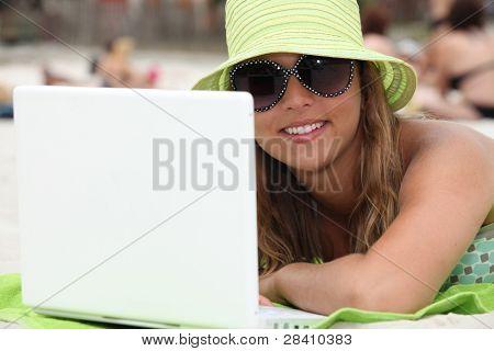 woman at beach using laptop