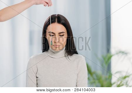 Cropped Shot Of Hypnotist With Pendulum Hypnotizing Young Woman With Closed Eyes