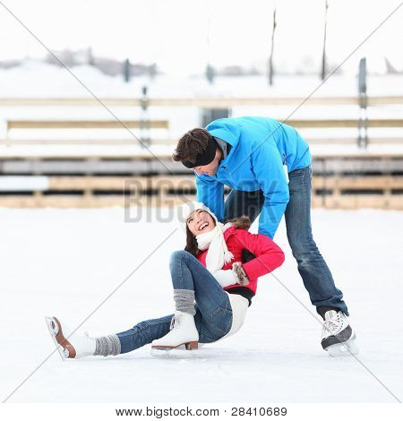 Ice skating couple having winter fun on ice skates in Old Port, Montreal, Quebec, Canada.
