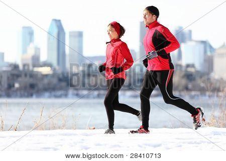 Läufer im Winterschnee mit Stadt Skyline Hintergrund ausgeführt. gesunde vielpunkt junges Paar. asiatische
