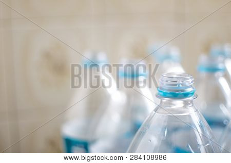 Pack Of Transparent Empty Pet Plastic Water Botles With Blue Label, No Cap And Blurred Background