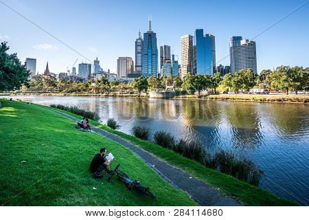 2nd January 2019, Melbourne Australia : Man Reading A Book On Yarra Riverbank Promenade Grass In Cen