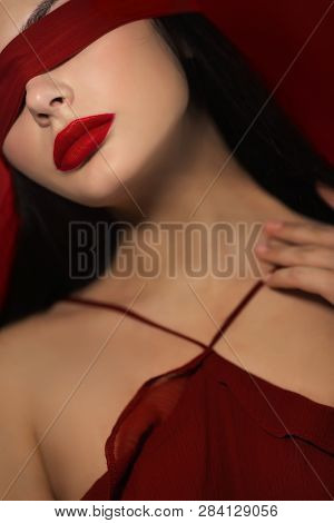 Beautiful Face With Ribbon On Eyes. Seductive Woman In Red Dress With Perfect Make-up Red Lips And R